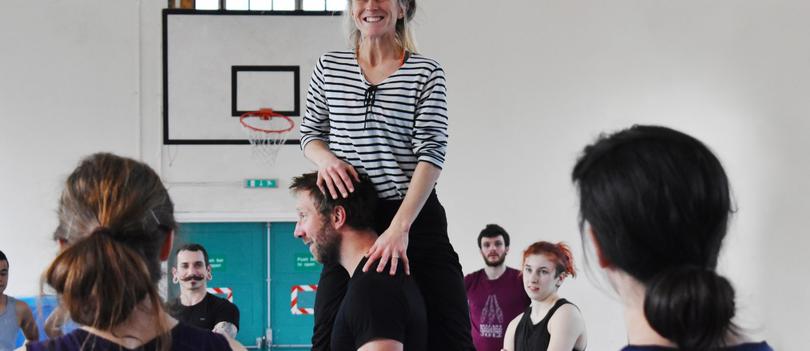 student balances on shoulder of another during circus class