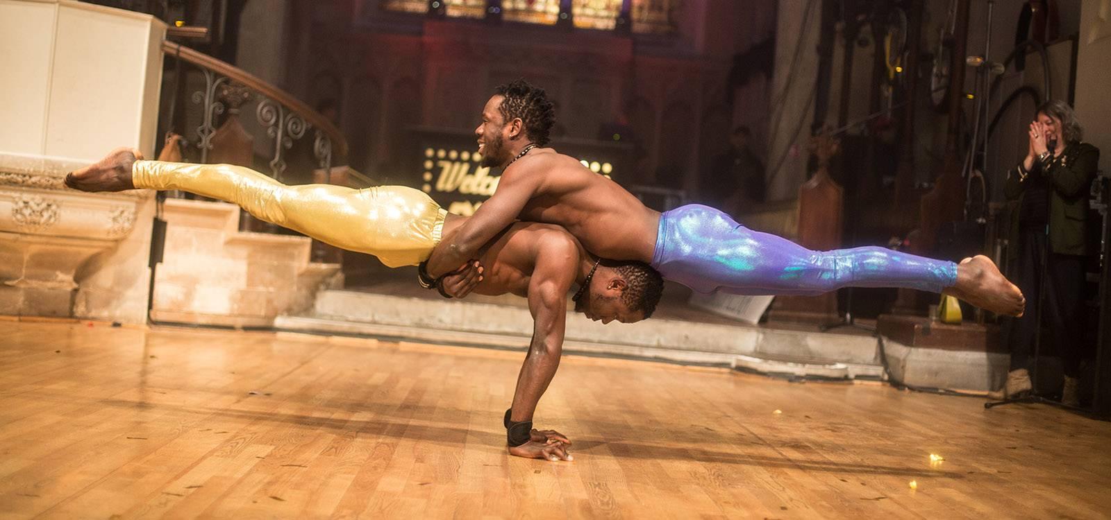 two circus artists performing a balancing act