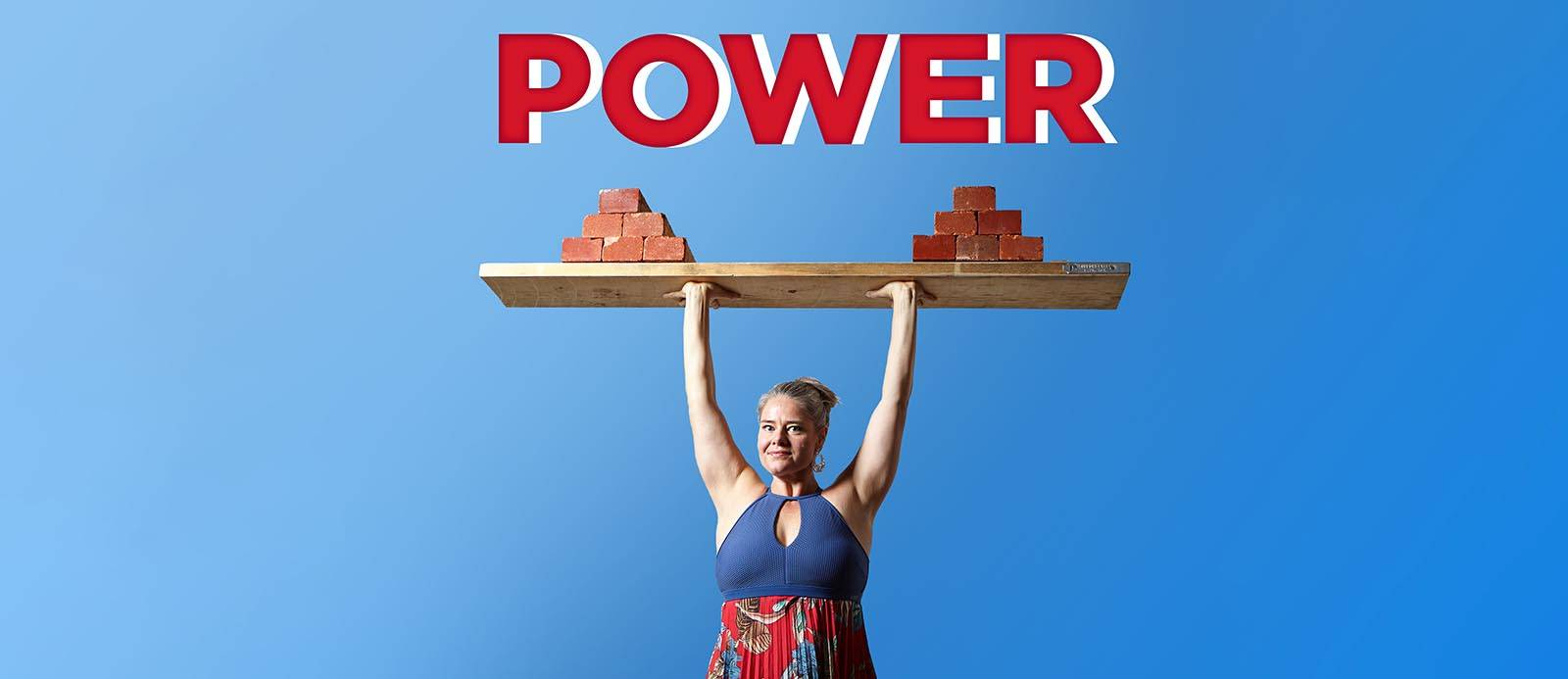 female weightlifter smiles while holding a plank piled with bricks